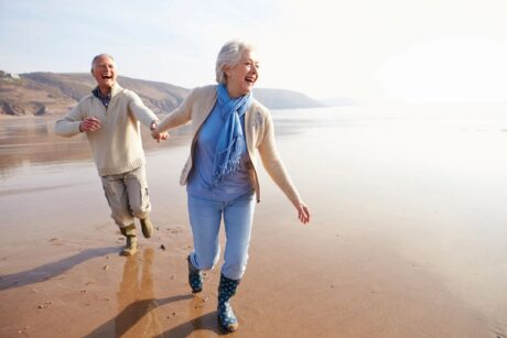 senior woman and man holding hands walking on beach