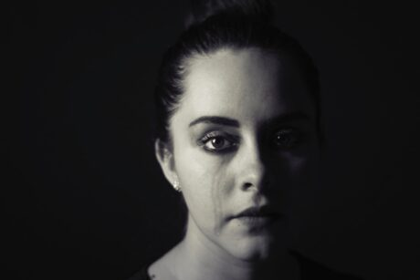 black and white image of womans face stained from tears