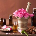 mortar and pestle full of roses surrounded by oil vials and flower petals