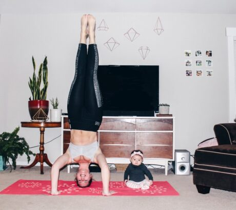 women doing headstand with baby sitting on floor next to her