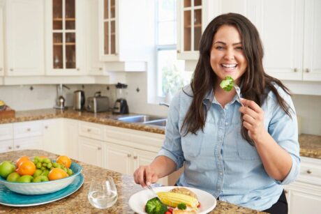 woman standing in kitchen smiling as she eats her healthy vegan lunch