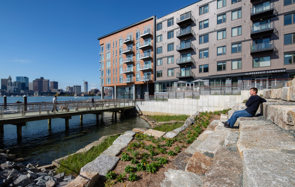 image of man sitting at the waterfront site of Clippership Wharf in East Boston