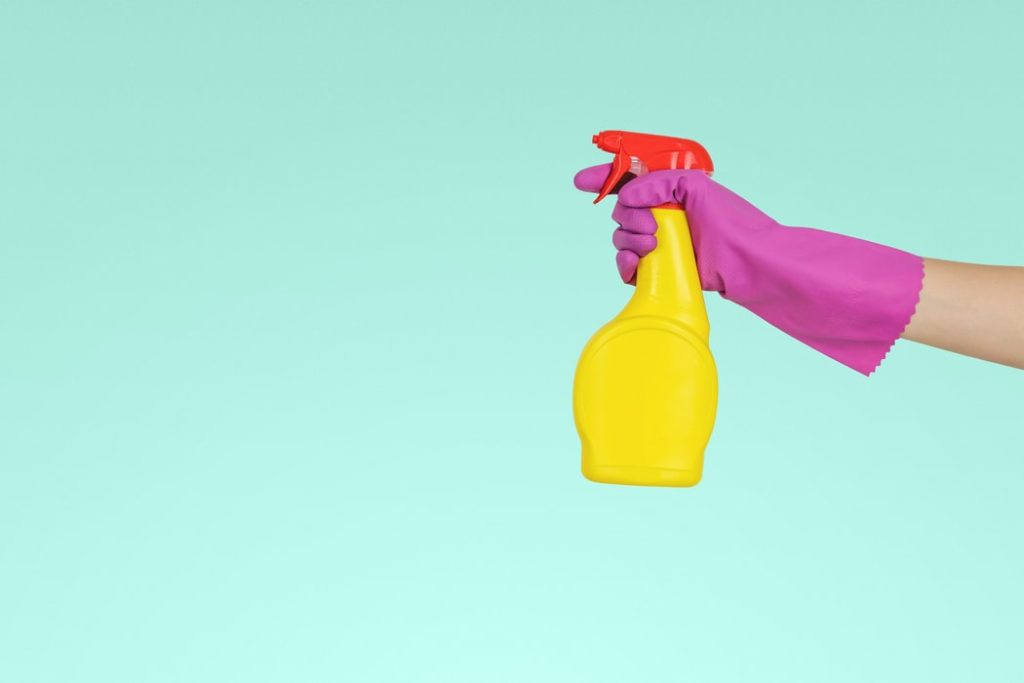 woman holding a spray bottle with pink gloves on with a blue background