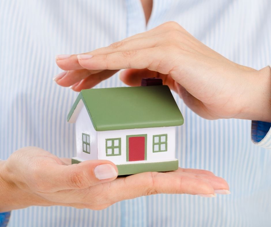 woman holding a home in the palm of her hands