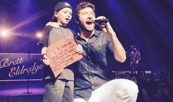Little boy brought on stage by Brett Eldredge rounds out his summer with two more big names
