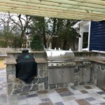 Outdoor kitchen with built-in appliances and pergola
