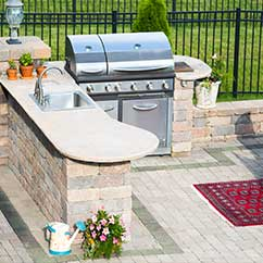 Outdoor kitchen area with grill and sink