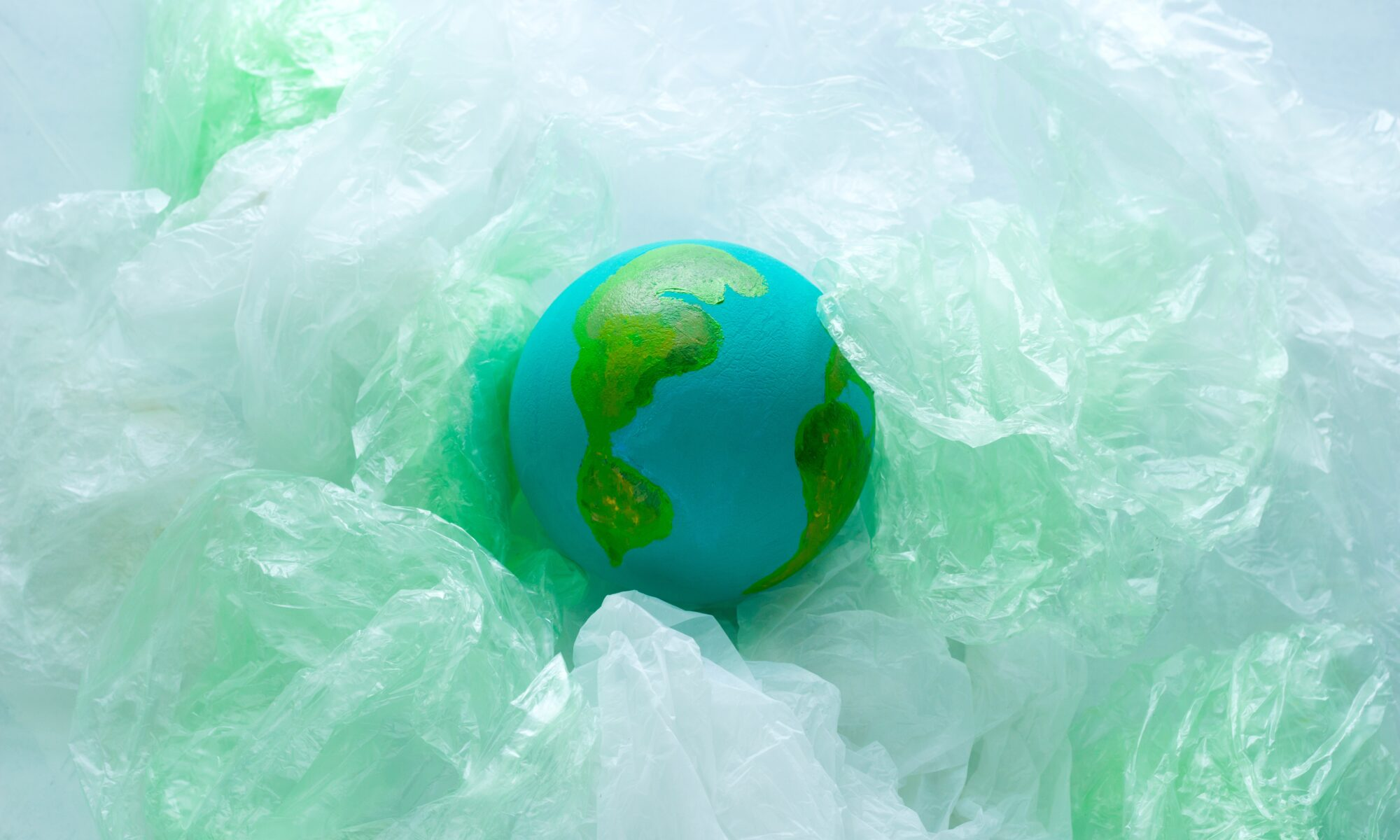 top view of a small model of the Earth planet among plastic bags, environment, global pollution concept, earth day