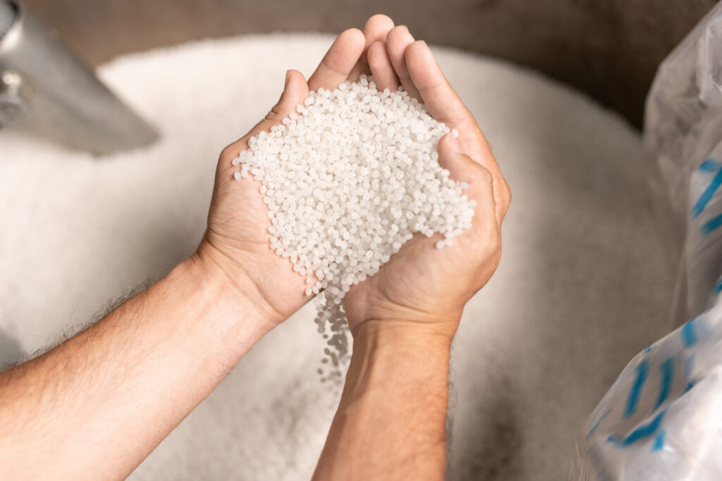 factory worker hands holding pile of white polymer pellets during working process