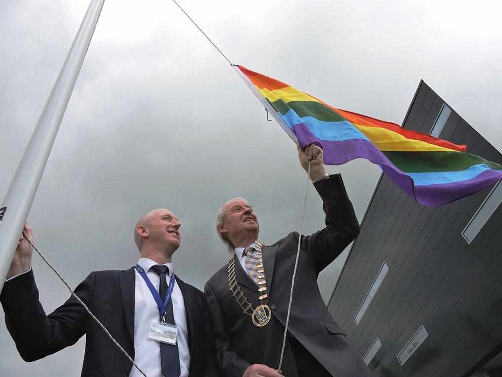 Councillor James Breen, Cathaoirleach of Clare County Council and Jason Murphy, Senior Executive Officer, Clare County Council raise the Pride Flag