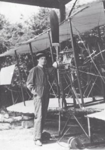 Woman in overalls standing in front of an early bi-plane