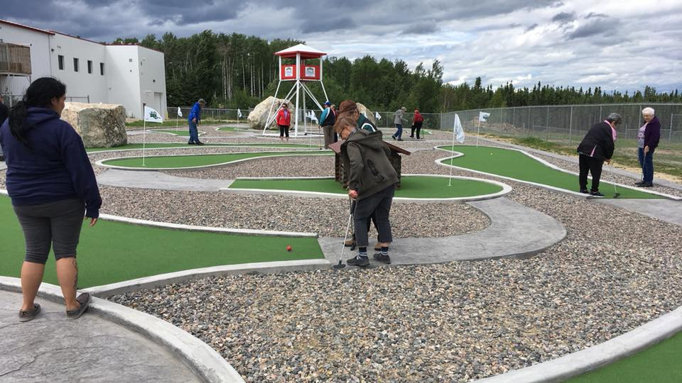 A picture of some elders playing mini golf and enjoying their time outside.