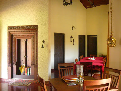 The dining area is decorated with hanging brass lamps, nooks and crannies, and a lovely old ornamental door