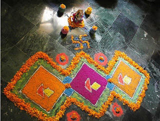 the attractive rangoli made by color powder, flowers, diya, grains and dried legumes
