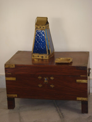 An old wooden treasure chest, with a brass and glass decorative lantern