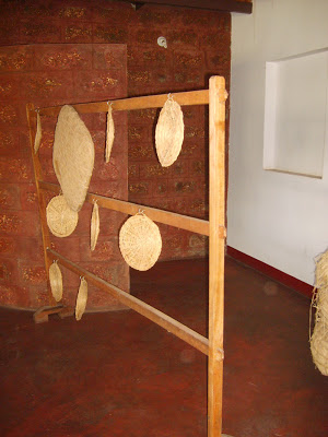 These flat decorations on the wooden frame are called 'kudupu' or 'thatti kudupu' and they are used as lids on vessels