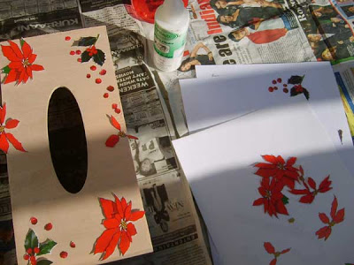 Arrange the cut out poinsettia pictures on the tissue box