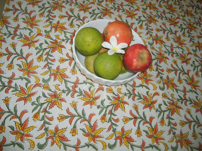the blockprinted tablecover and bowl of fruits on dining table