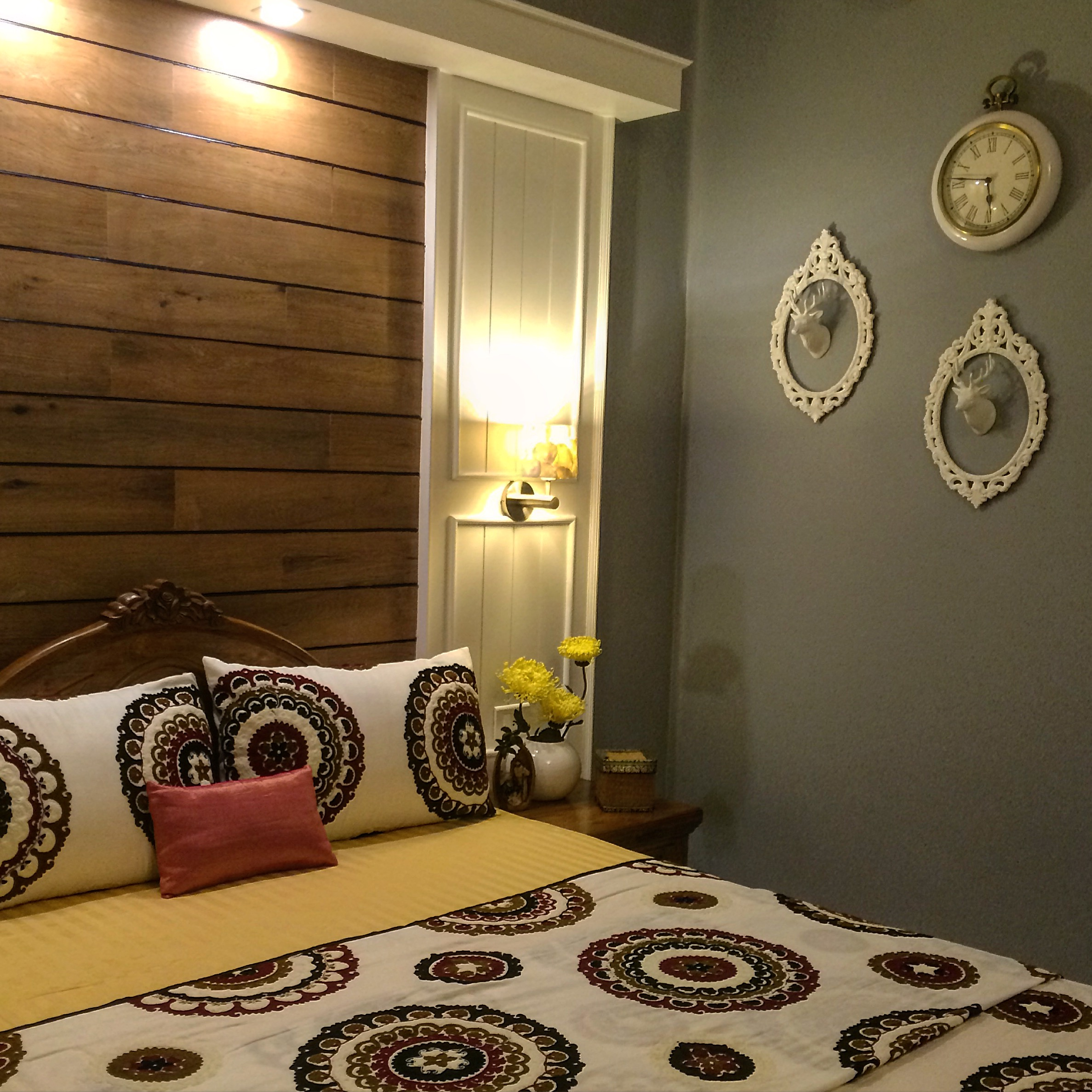 The guest room are decorated with frames on the wall with the beautiful deer heads on it, the embroidery on the bed covers and grey wall | Joseph home tour