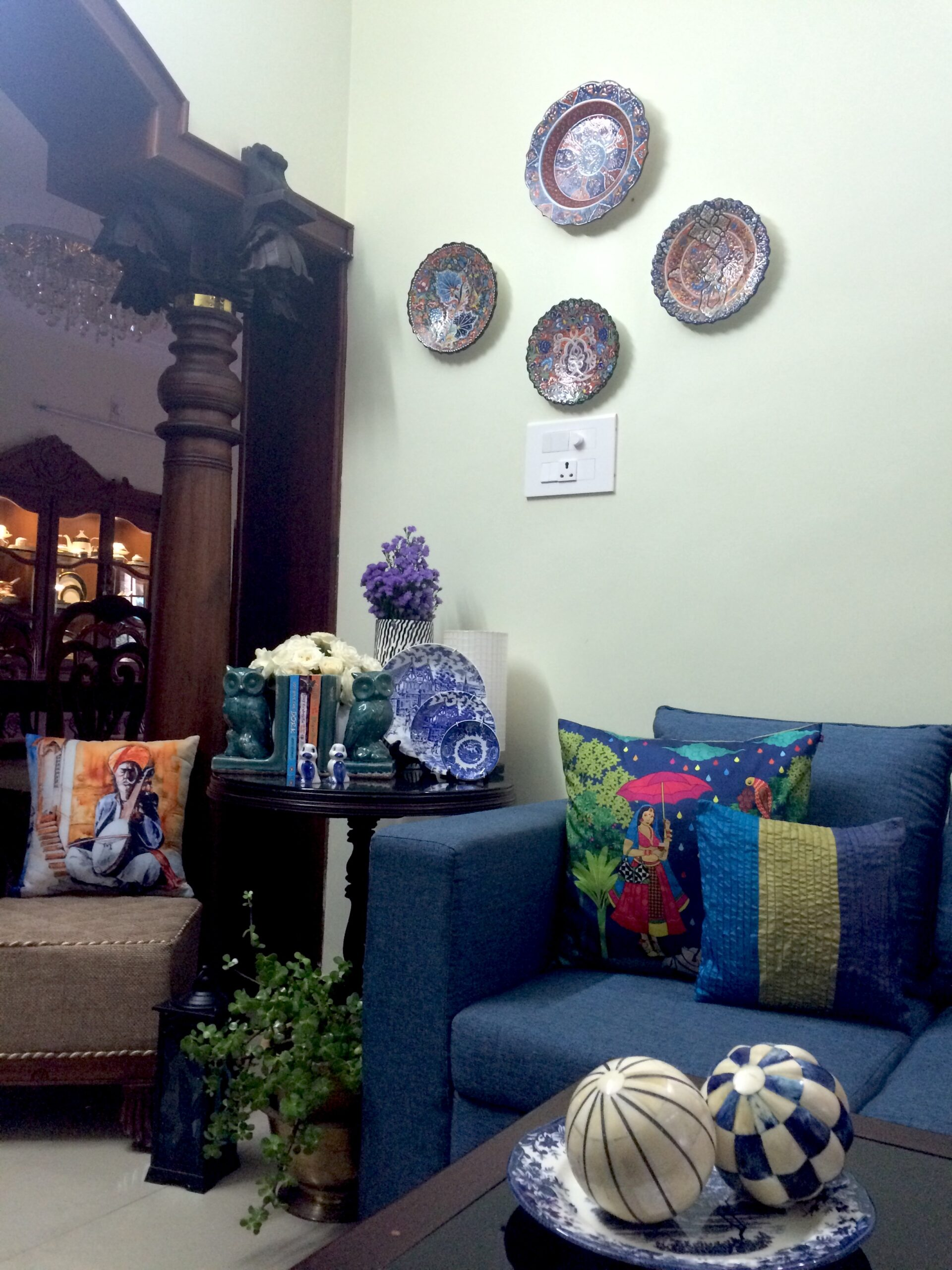 The blue room is decorated with blue wall plates, lanterns, blue sofa, green plants, cushion covers and antique wooden pillars | Joseph home tour
