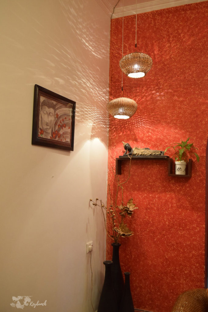 Home decor Tour by Ankita and Sitanshu's in Lucknow - the orange accent wall shelves adorned with plants and artifacts