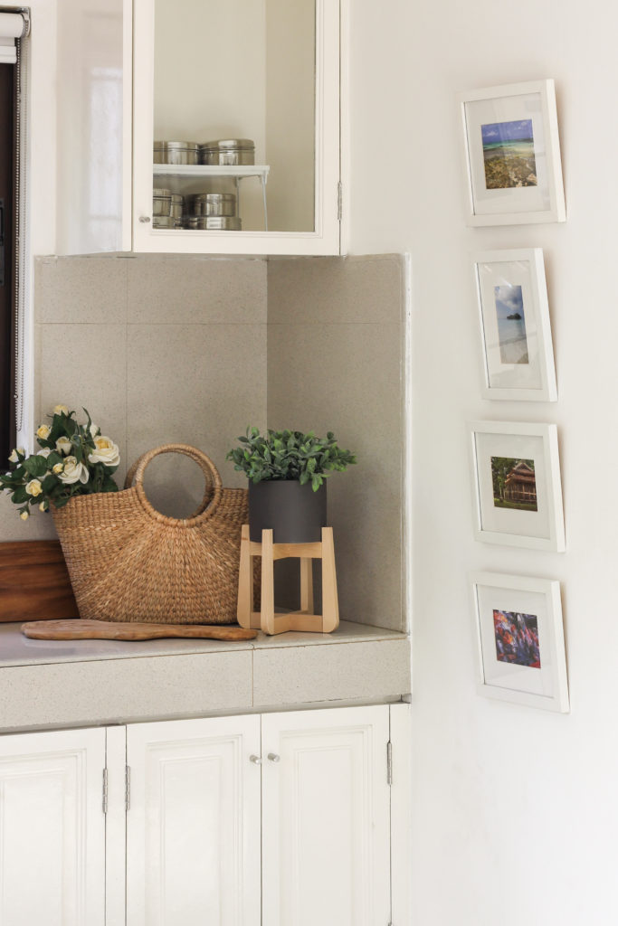 Home Tour with Kaho of Chuzai Living - A corner of the kitchen cabinet filled with basket, green plants and wall frames