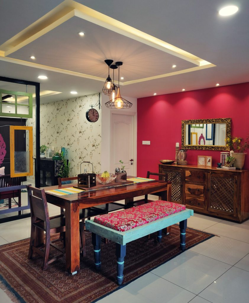 Home style Tour with Rajni in Hyderabad: the dining room is filled with beautiful colorful frames, green plants, decorative mirror, cabinet and vintages