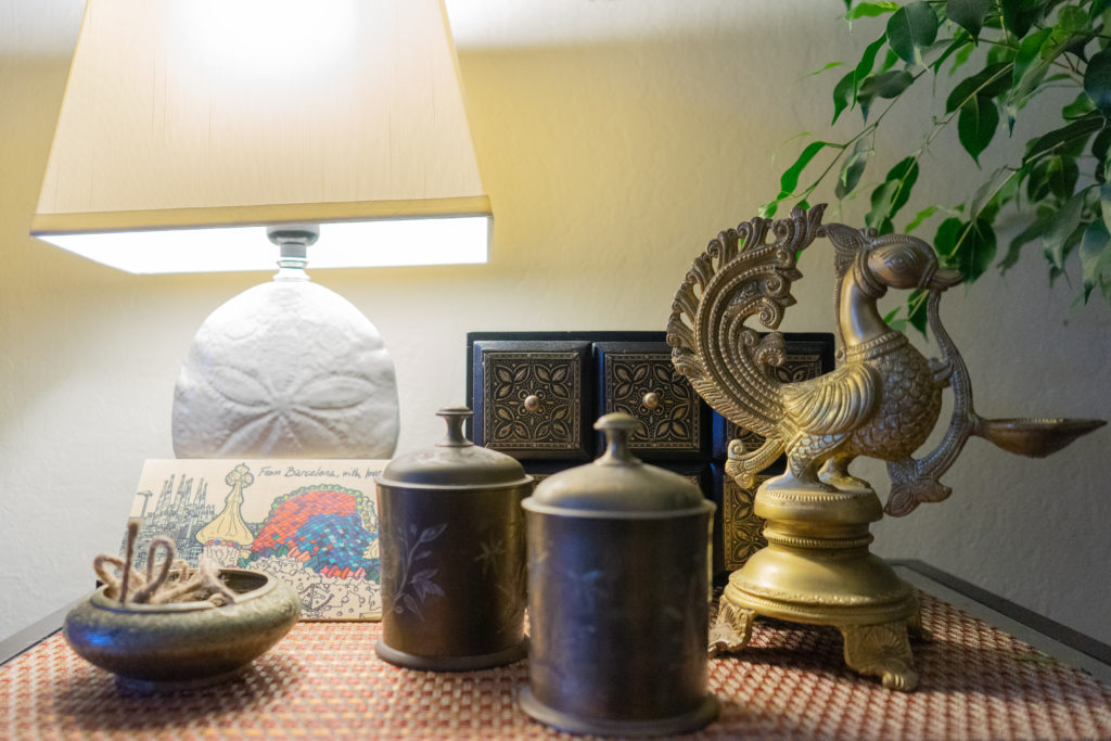 Affinity for antiques home tour of Rushika & Dipkal's - the collection of green plant, lamp, bronze, brass bowl and diya at the corner of the living room