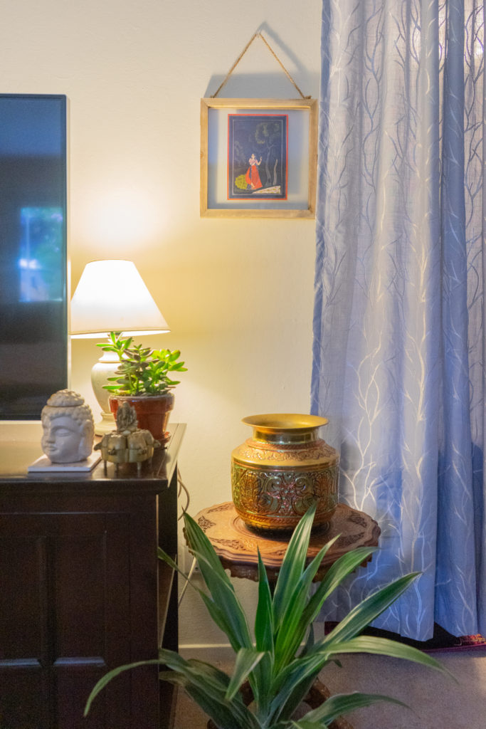 Affinity for antiques and collection of vintage | Home tour of Rushika & Dipkal's - the collection of brass pot, buddha, oil painting, lamp, and plants at the corner of the living room