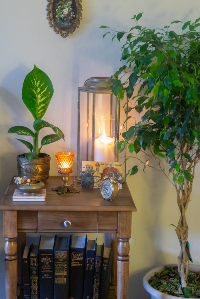 Affinity for antiques and collection of vintage | Home tour of Rushika & Dipkal's - the collection of brass bowl, antique clock, lantern, candle stands and green plant on the table