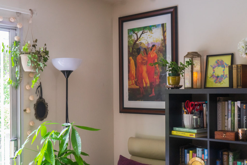 Affinity for antiques and collection of vintage | Home tour of Rushika & Dipkal's - the oil painting, indoor green plants, candle stand, book shelf and vintages at the living room