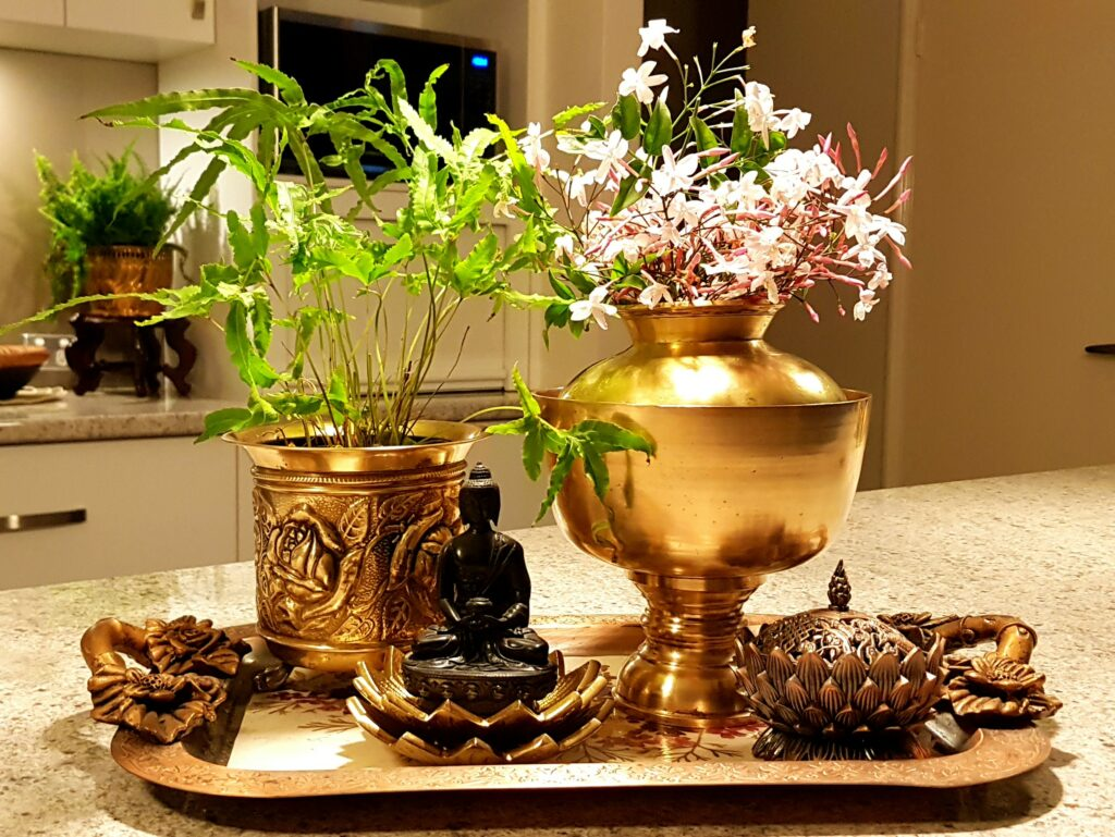 The table is setting up with fresh flowers and green plant in a brass-vase