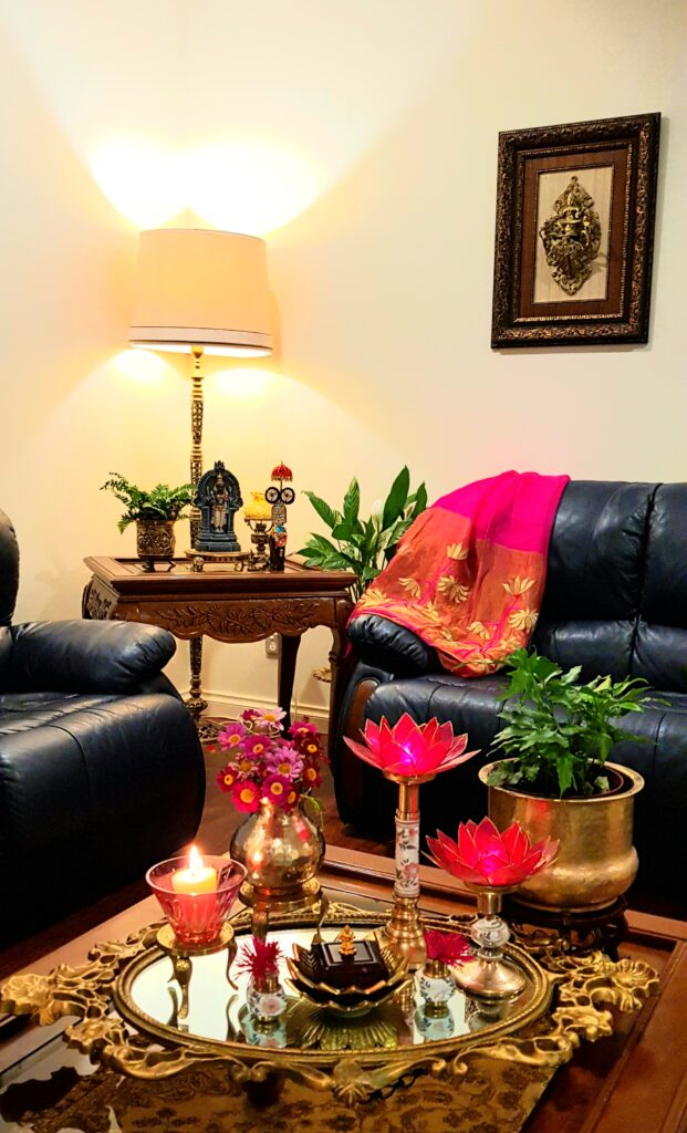 The living room is decorated with fresh flowers, glass candle stand, green plants, lotus candle stand, brass collection and vintage items