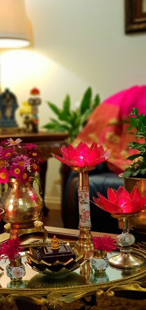 The table in the living room is setting up with fresh flowers, lotus candle stand and brass collection on it
