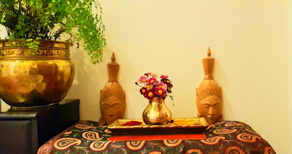 Fresh flowers, buddha wood sculpture and green plants at the corner of the room