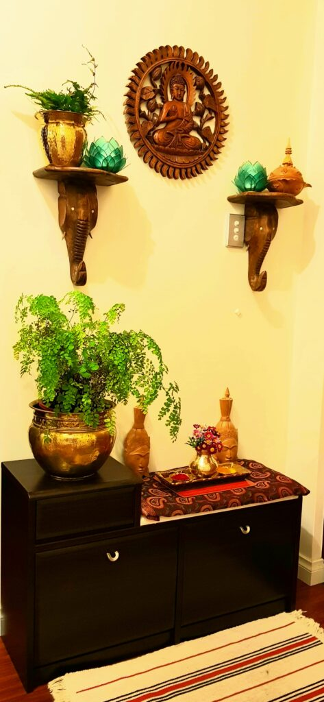 hand carved wood buddha frame, brass collection, green plant at brass vase at the corner of the room