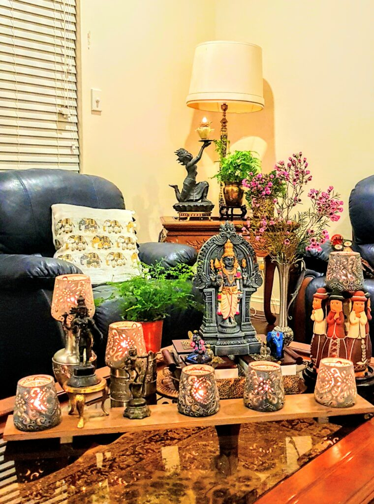 The table in the living room is decorated with diwali metal diyas, fresh flowers, sculpture and green plants