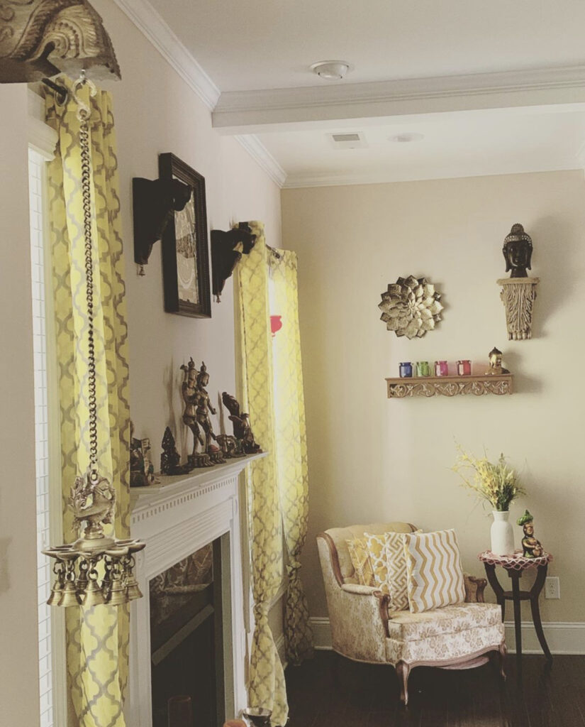 The corner of the room is decorated with vintage brass, wall frame, buddha sculpture, fresh flowers and chair