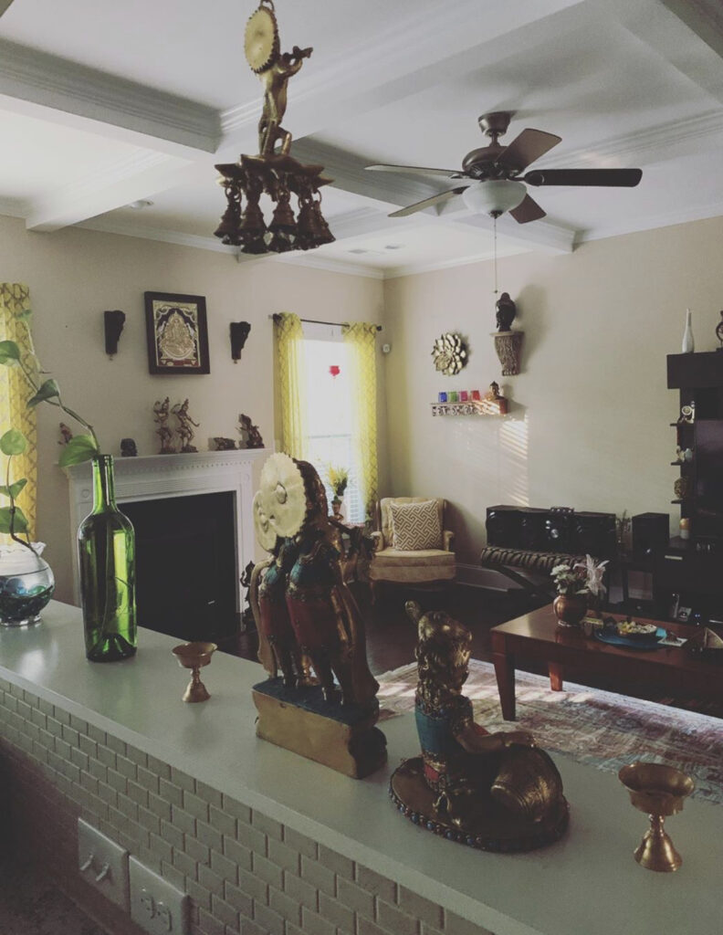 The corner of the living room is filled with brass collection, wall frame, green plants and vintage items