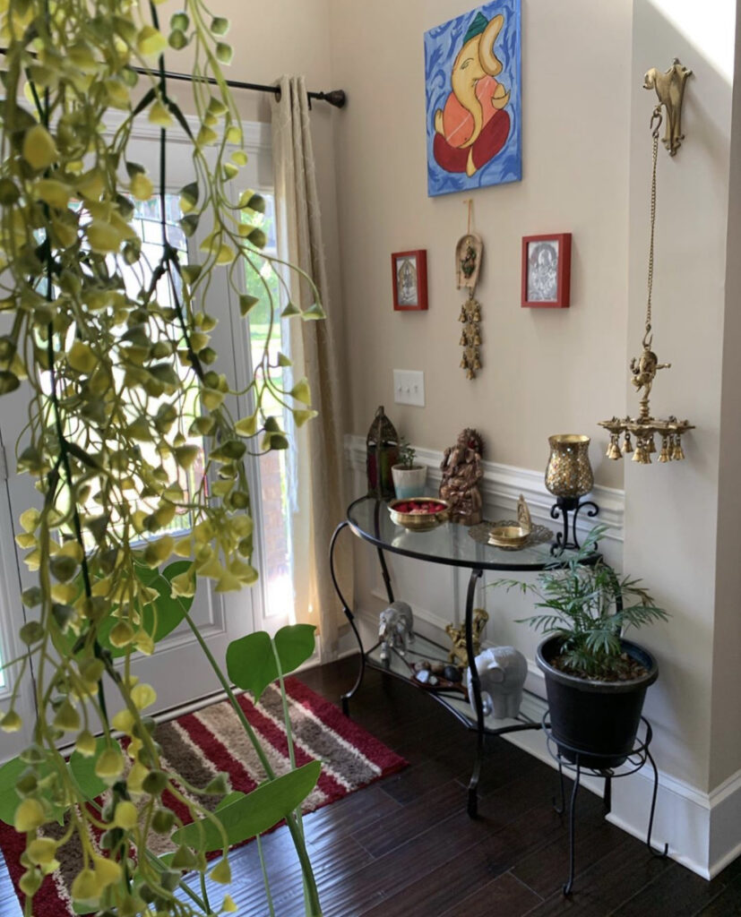 The entry way is decorated with green plants, vintage items, brass diyas and wall frames