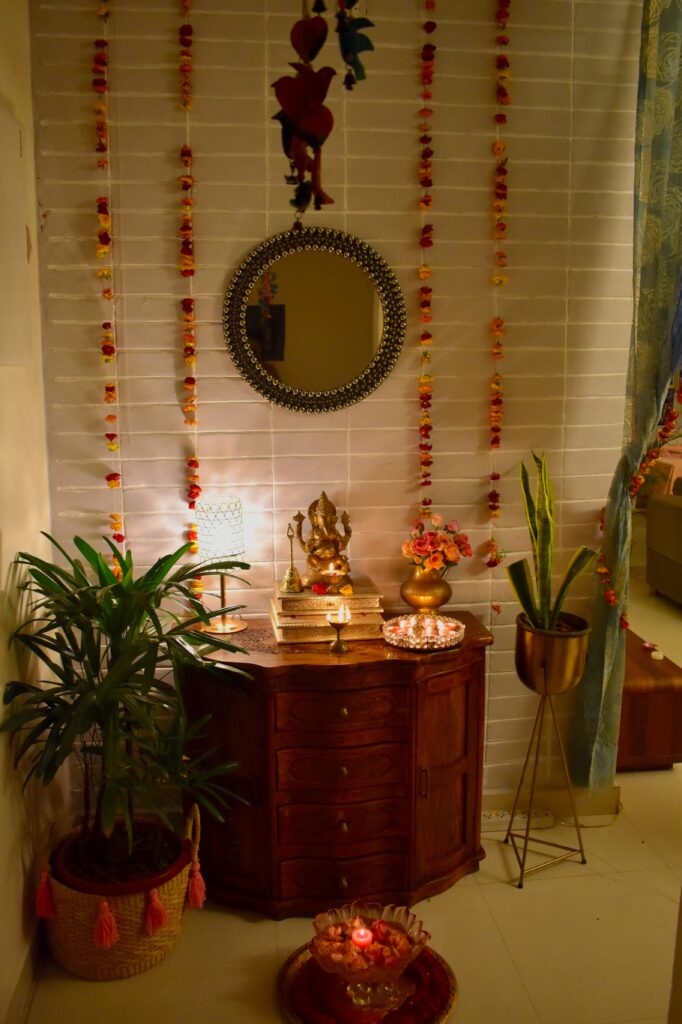 the pooja room is decorated with fresh flowers, lamp, diya, ganpati and green plants