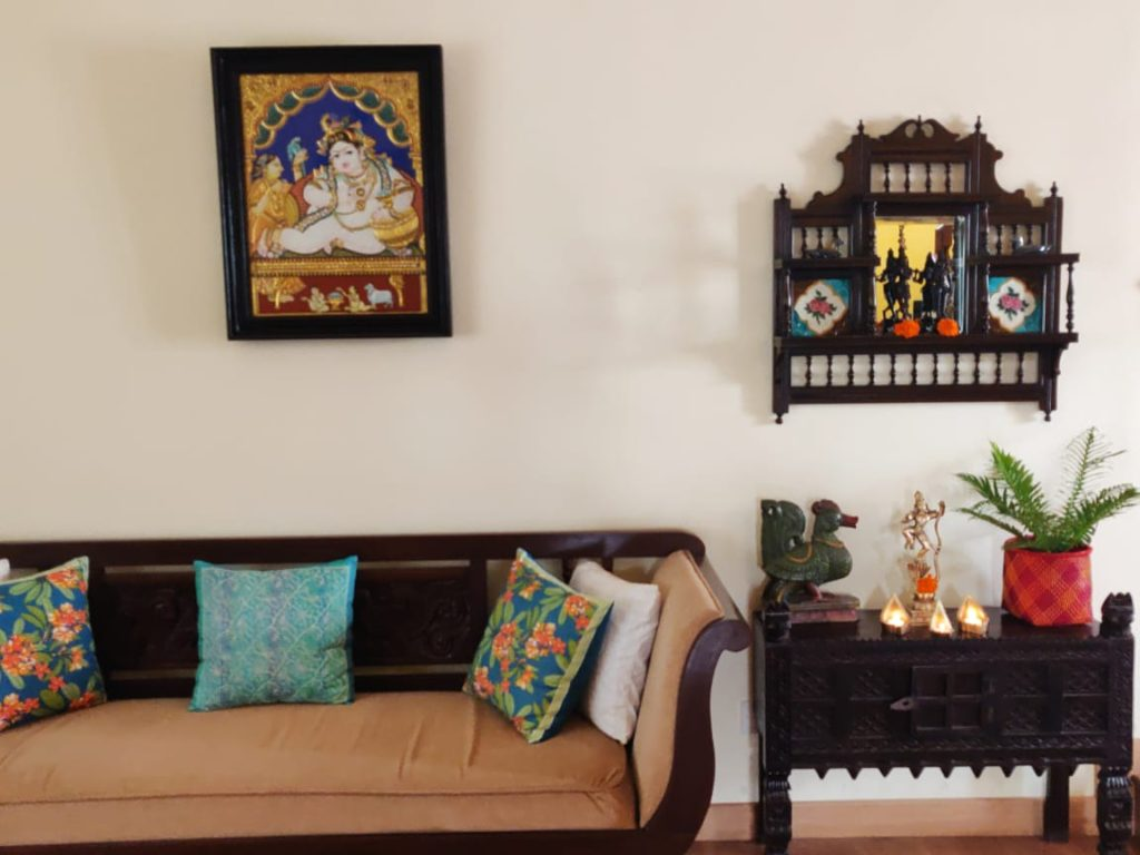 The vintage mirror, wall frame, diyas, green plants and sculpture at the corner of the living room