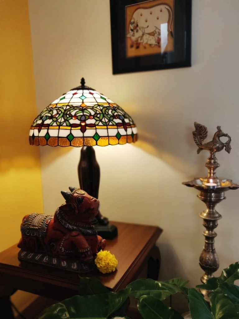 diya brass, lamp, bull sculpture, pichwai frame and green plants decorated at the corner of the living room