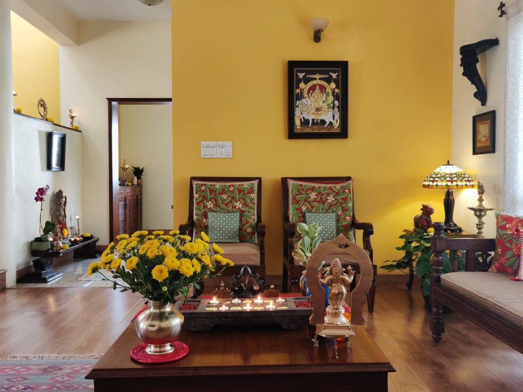 the living room is decorated with  brass, sculpture, green plants, fresh flowers and wooden diya stand and wall frames
