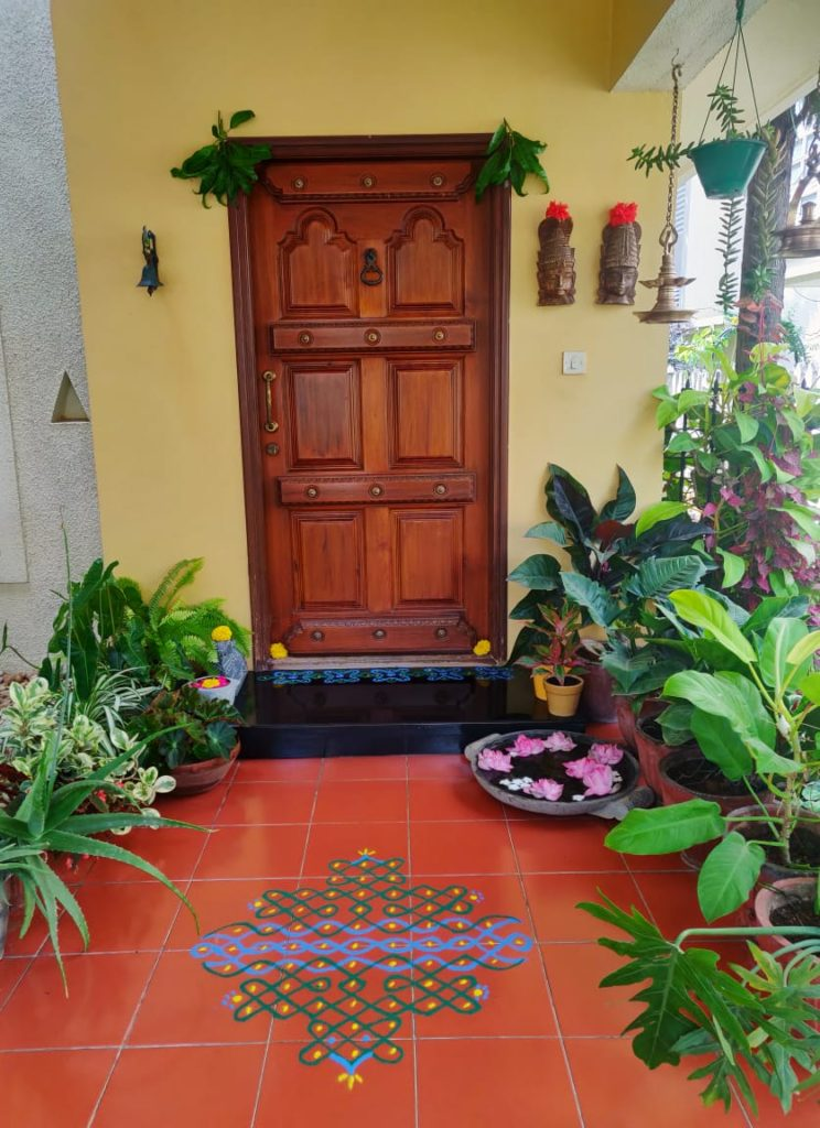 the beautiful indoor and outdoor green spaces, hanging brass diyas, mask wall decor and rangoli at the front door