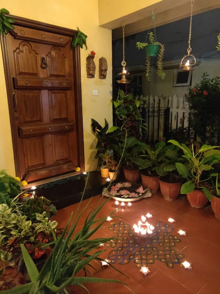 The front door entry is surrounded by green plants, and decorated with rangoli and light diyas for welcoming the diwali festival