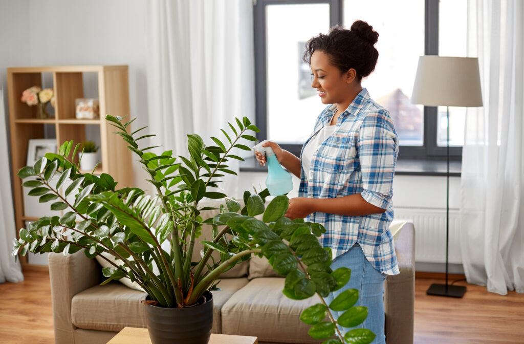 happy woman spraying houseplant with water sprayer at home.