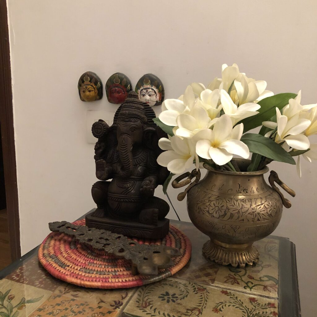 the top table is decorated with little fabric squares displayed under the glass, ganesha, fresh flowers on brass vase and brass spoon | Vintage Modern Indian decor | theKeybunch decor
