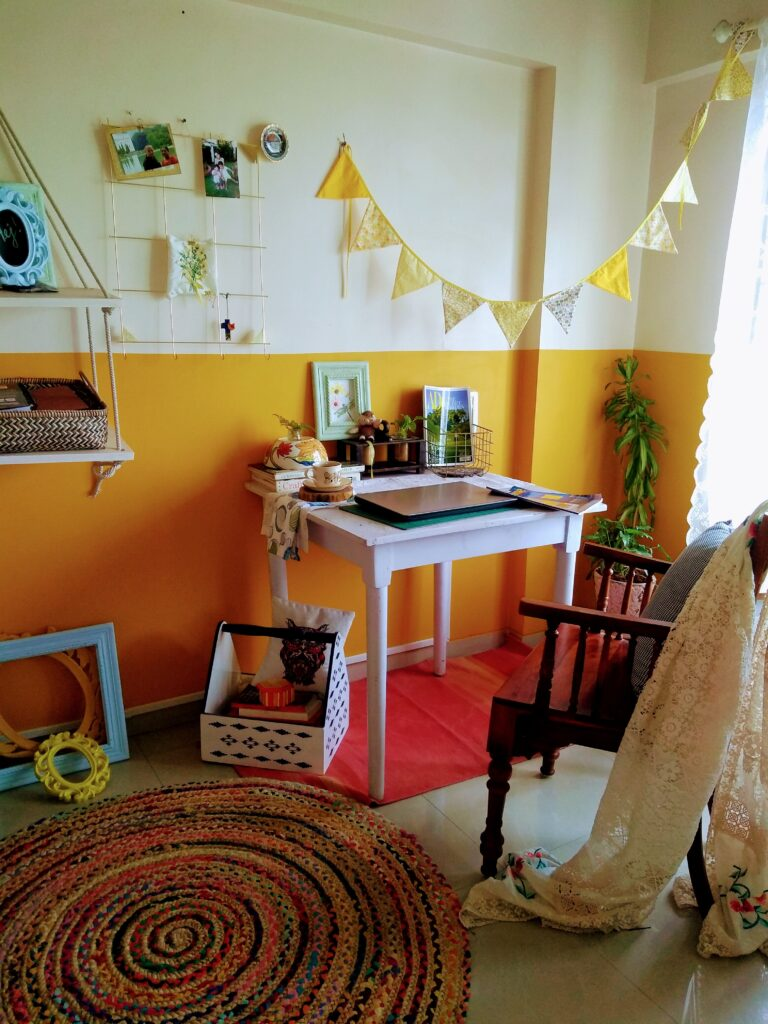 the bright yellow half painted wall, and an old dining table in white | home office set up