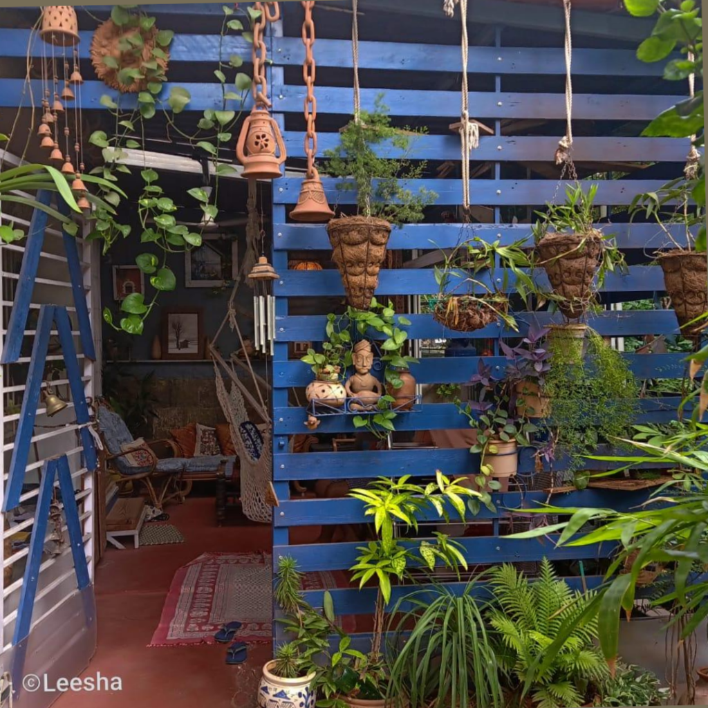 The assortment of lamps and terracotta bells at a blue slatted structure is decorated outside seating area | Leesha's Pune home | Thekeybunch